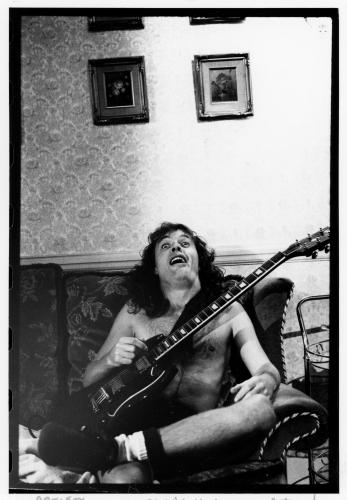 Angus Young of AC/DC sits on a sofa in his hotel. London 1986
