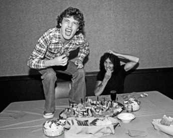 Angus Young and Bon Scott of AC/DC at lunch 1977.