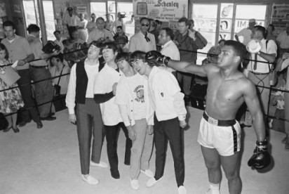 Boxer Muhammad Ali playfully hits The Beatles while at his training camp. From left to right: Paul McCartney, John Lennon, Ringo Starr, and George Harrison.