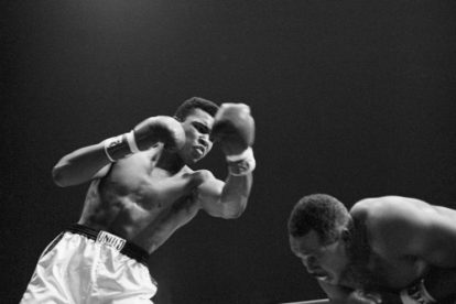 Cassius Clay throws a left punch to Archie Moore who ducks below the punch, during the fight at the Sports Arena in Los Angeles, California. Cassius Clay won by KO in round 4 of 12.