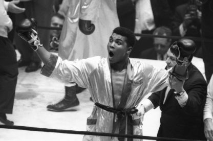 Cassius Clay celebrates his win, throwing his arms up in the air after winning against Doug Jones during their heavyweight bout at Madison Square Garden, New York.
