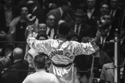 Cassius Clay celebrates his win, throwing his arms up in the air after winningagainst Doug Jones during their heavyweight bout at Madison Square Garden, New York.