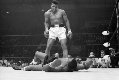 Heavyweight champion Muhammad Ali stands over Sonny Liston and taunts him to get up during their title fight.
