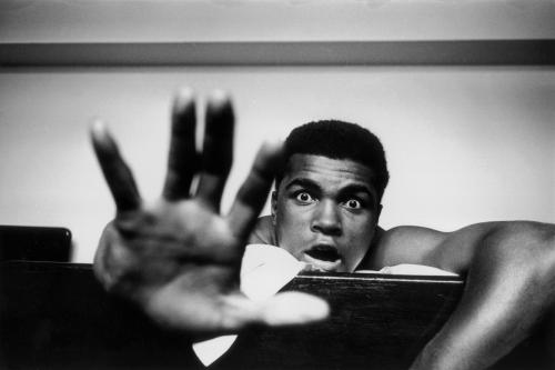 American Heavyweight boxer Cassius Clay (later Muhammad Ali) lying on his hotel bed in London. He holds up five fingers in a prediction of how many rounds it will take him to knock out British boxer Henry Cooper.