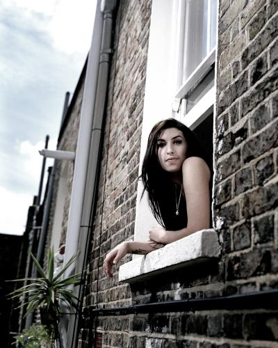 Amy Winehouse looks out of a window.