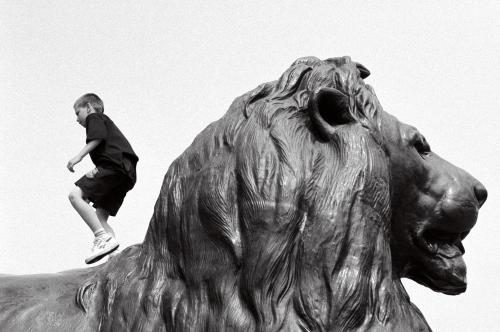 A boy climbes on one of Trafalgar Sqaure's lions. Photograpged in 1993 by Barbara Chandler Sonic Editions print