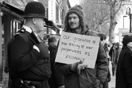 A man with a sign that reads 'Our ignorance of the reality of war perpetuates its existence' talks to a policeman on Chiswick High Road