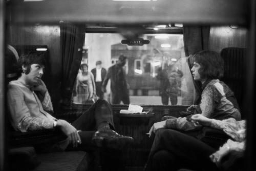 Paul McCartney of the Beatles and Mick Jagger of the Rolling Stones sit opposite each other on a train at Euston Station