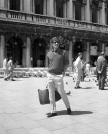 French actor Jean-Paul Belmondo, wearing a striped shirt, a sweater and sunglasses standing in St Mark Square, Venice.