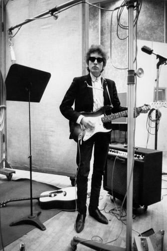 Bob Dylan plays a Fender Stratocaster electric guitar through an Ampeg amplifier while recording his album 'Bringing It All Back Home' on January 13-15