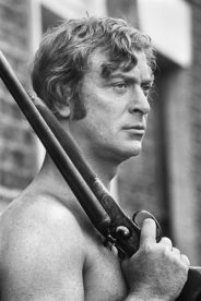 British actor Michael Caine toting a shotgun topless on the set of 'Get Carter', 1970.