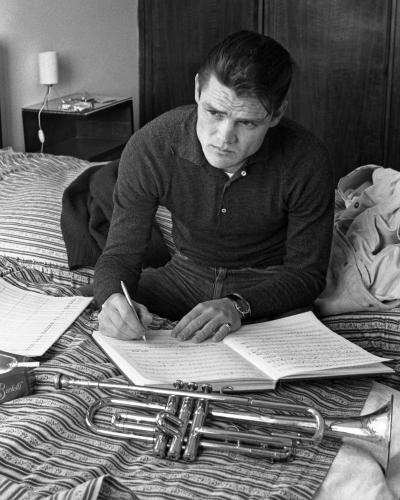 American jazz trumpeter Chet Baker sitting on a Lucca Hotel bed