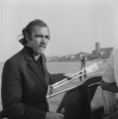 Actor Sean Connery portrayed on a water taxi in the Venetian lagoon with Venice in the background