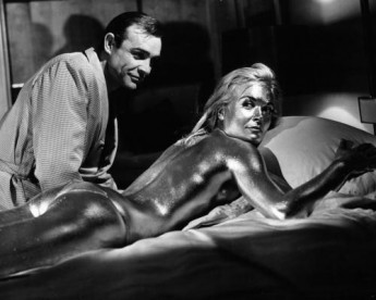 Sean Connery sitting next to Shirley Eaton as she lies on her stomach with her whole body covered with gold spray in a scene from the film 'Goldfinger'