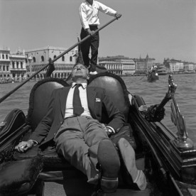 American actor Gary Copper, wearing a blazer and tie, laying down on a gondola, a gondalier rowing behing him, St. Mark's Basin, Venice.