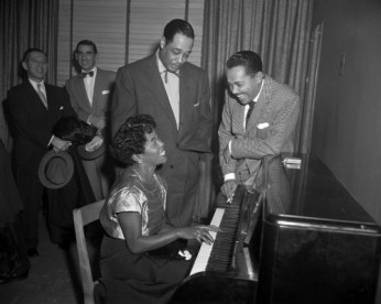 Jazz Singer Sarah Vaughan plays piano as bandleader Duke Ellington and singer Billy Eckstine watch