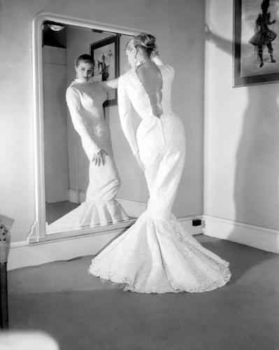Swedish actress Anita Ekberg examines her reflection as she tries on the sheath-like gown that she will wear for the royal film performance at Leicester Square
