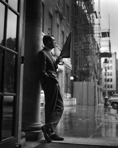 British-born American actor Cary Grant (1904 - 1986) sheltering in a hotel porch as he waits for the rain to stop.
