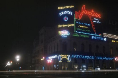 View of neon signs advertising liquor and clothing brands at night in Havana