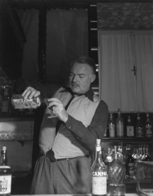 Ernest Hemingway standing behind a bar counter pouring gin from a bottle of Gordon's