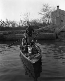 American writer Ernest Hemingway sitting on a boat, riffle in hand hunting ducks in a pond, in Torcello Island, Venice.