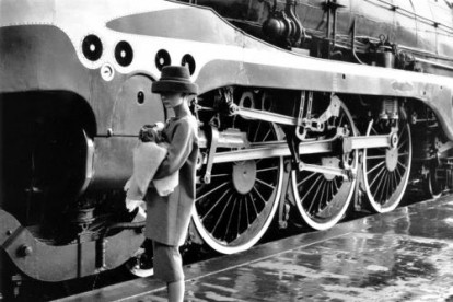 Audrey Hepburn (1929-1993) on a railway platform beside a steam locomotive in a scene from the Paramount film 'Funny Face'.