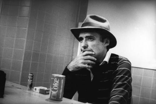 Dennis Hopper sat at a table looking thoughtful