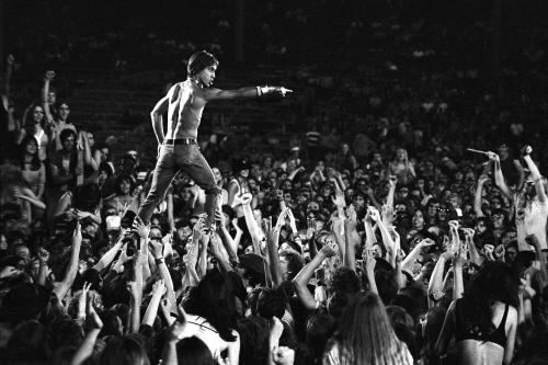 Iggy Pop being held up in the crowd by fans
