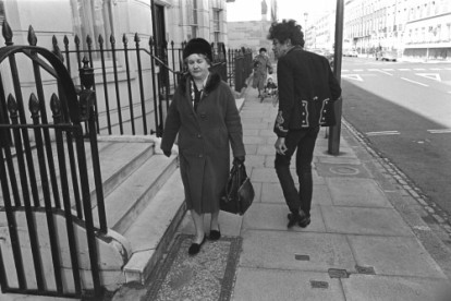 Jimi Hendrix passes an unimpressed woman walking down the street in London.