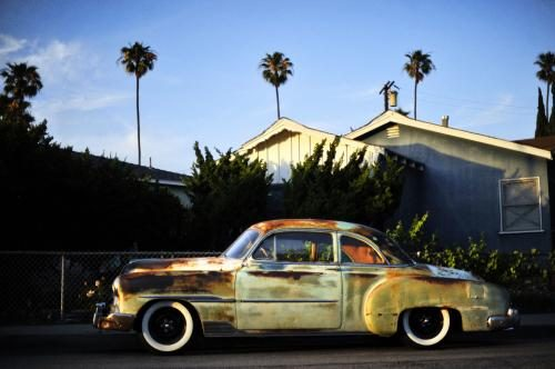 A rusty vintage car sits on a Los Angeles side street