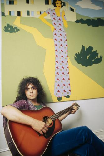 Marc Bolan (1947 - 1977) poses with a guitar in front of a painting at his home in 1972.