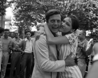 Italian actor Marcello Mastroianni hugs swedish actress Anna Karina while surrounded by photographers during the Venice Movie Festival, Lido, Venice.