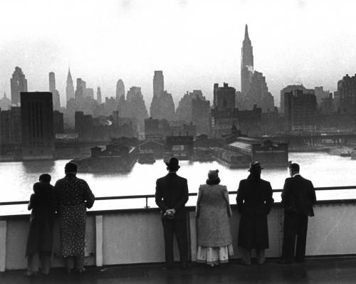 Passengers on board the Cunard White Star liner Queen Mary view the New York skyline as the ship docks in Manhattan at dawn.