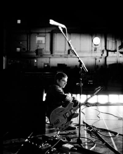 """Noel Gallagher sitting on the stage on the set of """"The Hindu Times"""" video filmed at Abbey Road Studios"""