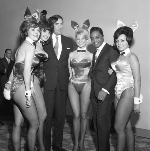 Actor Gregory Peck and rock and roll singer Jackie Wilson poses for a portrait with a group of Playboy Bunnies at a dinner for the Motion Picture Pioneers Association at the Playboy Club.