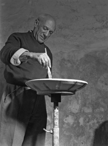 Spanish artist Pablo Picasso portrayed while decorating one of his ceramic dishes
