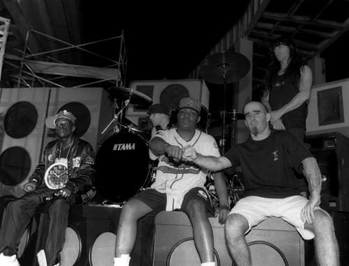 Rappers Flavor Flav and Chuck D. of Public Enemy pose on the set with members of Anthrax
