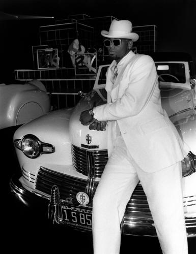 R.Kelly leaning on a Lincoln
