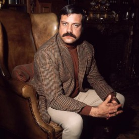 British actor Oliver Reed (1938 - 1999) sitting in an armchair in his huge ex-monastery home