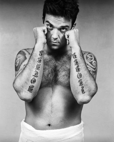 Robbie Williams shows off his tattoos.