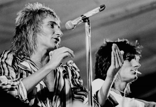 Rod Stewart & Ronnie Wood photographed mid performance on stage in 1975.