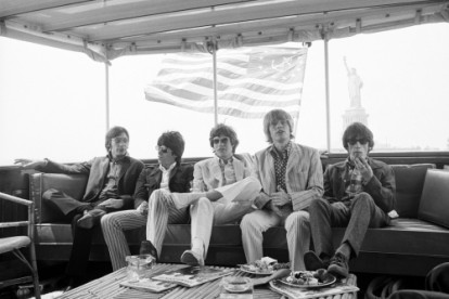 The Rolling Stones relax aboard a yacht while cruising along New York Harbor. The Statue of Liberty in the background.
