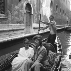 Mick Jagger sitting next to Bianca Jagger in a gondola while on their honeymoon
