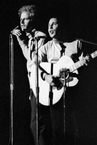 Paul Simon and Art Garfunkel photographed performing live on stage in 1968.