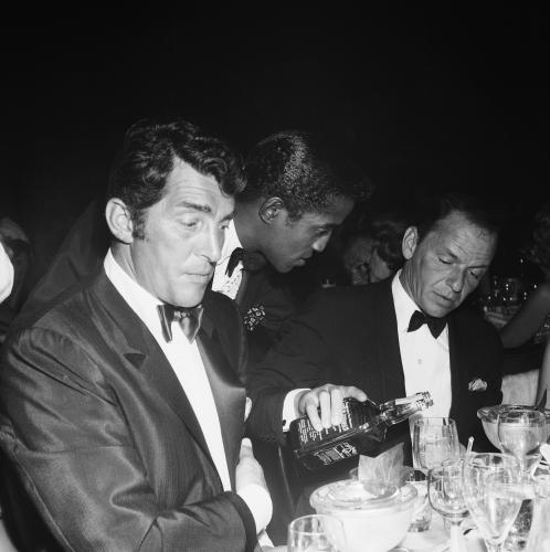 Dean Martin and Sammy Davis Jr. sit at a table while Frank Sinatra pours Jack Daniels from a bottle at the Coconut Grove during Eddie Fisher‰Ûªs opening night in Los Angeles.