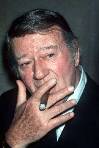 John Wayne smokes a cigar during a visit to London.