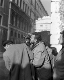 American film director Orson Welles, shooting with a cinecamera on the set of the movie Othello, filming next to the Ponte dei sospiri, members of the crew around him, Venice.