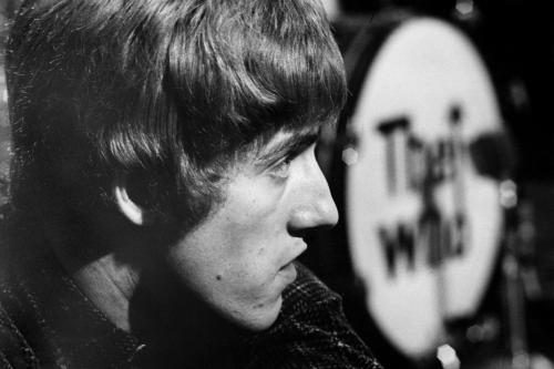 Roger Daltrey takes time out from performing. The iconic 'The Who' logo can be seen on the drum behind him.